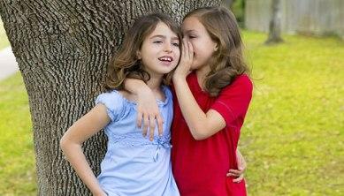 Girl whispering in another girl's ear